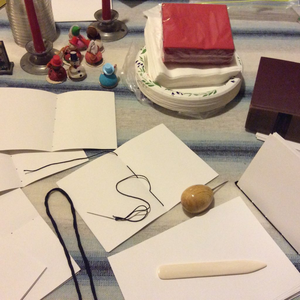 End journals for New Year's parties with an awl, paper folder, and heavy books for pressing